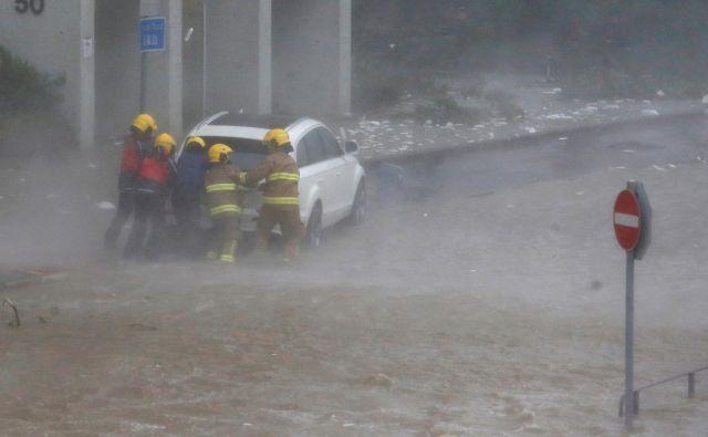 Gasilci pomagajo v poplavah ujetemu vozniku. FOTO: Bobby Yip/Reuters