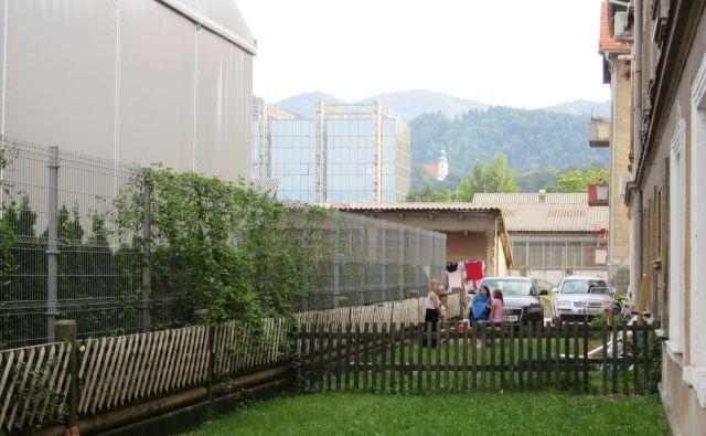 Orodjarna je s šotoroma (levo), ki ju je na črno postavila pred dvema letoma, stanovalcem Delavske 16 in 18 (skrajno desno) vzela še park. Inšpektor je aprila 2016 izdal odločbo, da je treba šotora odstraniti, a je izvršba odložena do 8. avgusta 2022. FOTO: Špela Kuralt/Delo