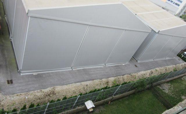 Orodjarna je s šotoroma (zgoraj), ki ju je na črno postavila pred dvema letoma, stanovalcem Delavske 16 in 18 (slikano z najvišjega nadstropja) vzela še park. Inšpektor je aprila 2016 izdal odločbo, da je treba šotora odstraniti, a je izvršba odložena do 8. avgusta 2022. FOTO: Špela Kuralt/Delo
