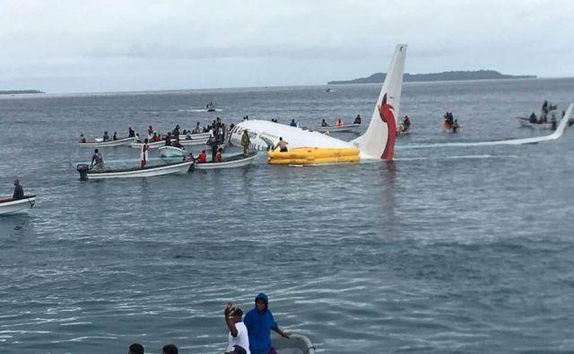 Takole so čolni prispeli do letala, ki je pristalo v vodi ob Mikroneziji. FOTO: James Yaingeluo/Reuters