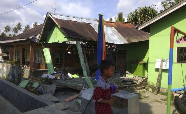 Indonezijska agencija za nesreče poroča o zrušenih objektih, cunami z 1,5 metra visokimi valovi je odnašal hiše. FOTO: AFP