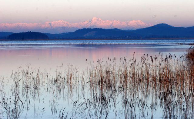 Takole je Cerkniško jezero videti pozimi, ko je napolnjeno z vodo. A tudi zdaj, ko vode skoraj ni, umirjena pokrajina v jesenskih odtenkih, zlasti gledano z višine, jemlje dih. Foto Mavric Pivk/Delo