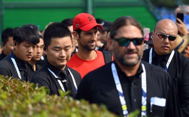 Novak Đoković (v Šanghaju na poti na trening ob številnih varnostnikih) je nared za zmagoviti finiš sezone. Foto: AFP