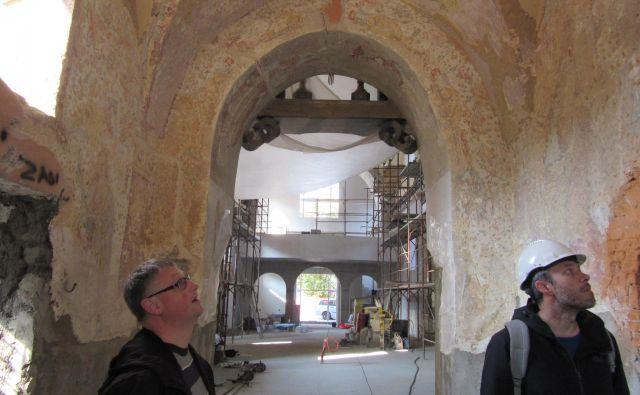 Župnik Tadej Linasi (levo) in višji konservator celjske enote ZVKDS Matija Plevnik si ogledujeta freske v zvonici. Zadaj je ladja cerkve z novim, večjim korom. FOTO: Špela Kuralt/Delo