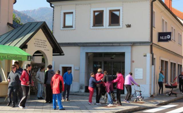 Pred bančno poslovalnico v Črni se zgrinjajo domačini. Prišli so tudi komitenti iz Centra za usposabljanje, delo in varstvo. FOTO: Mateja Kotnik