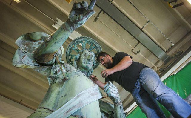 Obnovljeni kip nadangela Mihaela iz piranske cerkve in Jožef Drešar vodja projekta obnove kipa v restavratorski delavnici Gnom. Foto Jože Suhadolnik