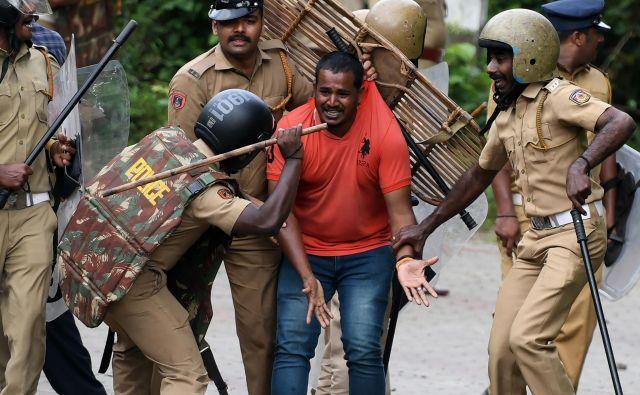 Indijska policija pretepa hindujskega aktivista med protestom zoper sodbo vrhovnega sodišča, ki je opustilo prepoved vstopa žensk v hindujski tempelj v indijskem mestu Nilackal. Spopadi so se začeli, ko so tradicionalisti poskušali preprečiti ženskam, da obiščejo enega izmed najsvetejših templjev hinduizma. Foto Arun Sankar Afp