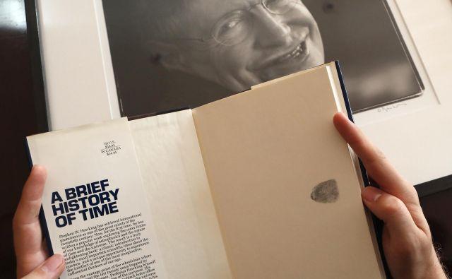 Knjiga Kratka zgodovina časa s prstnim odtisom avtorja Stephena Hawkinga. FOTO: Frank Augstein/AP
