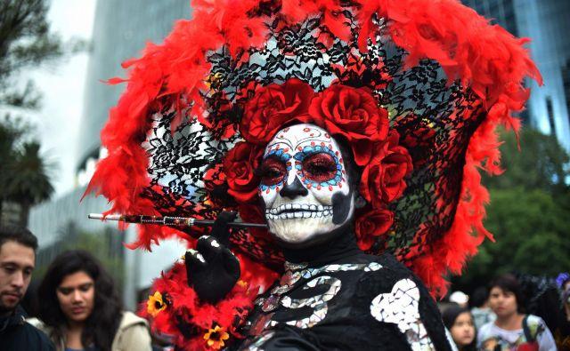 """Mehičani preoblečeni kot """"Catrina"""" na paradi """"Catrinas"""" v Mexico Cityju. Mehičani se pripravijo na praznovanje dneva mrtvih. Lik la Catrine je ustvaril karikaturist Jose Guadalupe Posada, znan po svojih risbah tipičnih lokalnih, folklornih prizorov, družbeno-politične kritike in ilustracij okostnjakov ter lobanj, vključno z La Catrino.Foto Rodrigo Arangua Afp"""