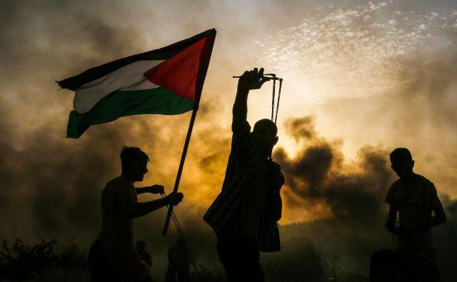 Palestinski demonstrant drži nacionalno zastavo, ko drugi protestnik meče kamen proti izraelskim silam med spopadi na plaži blizu morske meje z Izraelom na severu Gaze. Foto Mahmud Hams Afp