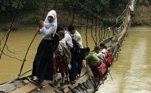 Otroci morajo po uničenem visečem mostu, ki je edina možna pot do šole v odročni indonezijski provinci.Foto Beawiharta Beawiharta Reuters