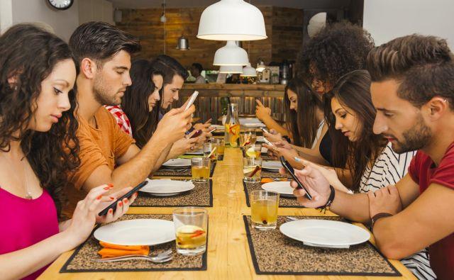 Namesto pogovora strmenje v mobilni telefon? Navada, ki se mnogim zdi že običajna, druge pa jezi.<br /> <br /> FOTO Shutterstock