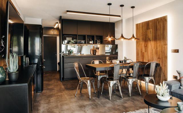 Kuhinja je majhna, a dovolj velika, da ima vse za udobno kuhanje. Na videz jo nekoliko povečajo ogledala na steni med zgornjimi in spodnjimi omaricami. Foto: Anže Vrabl