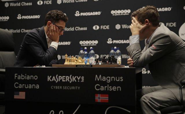 Magnus Carlsen (desno) v dvoboju za naslov svetovnega prvaka v Londonu s Fabianom Caruano. FOTO: Matt Dunham/AP