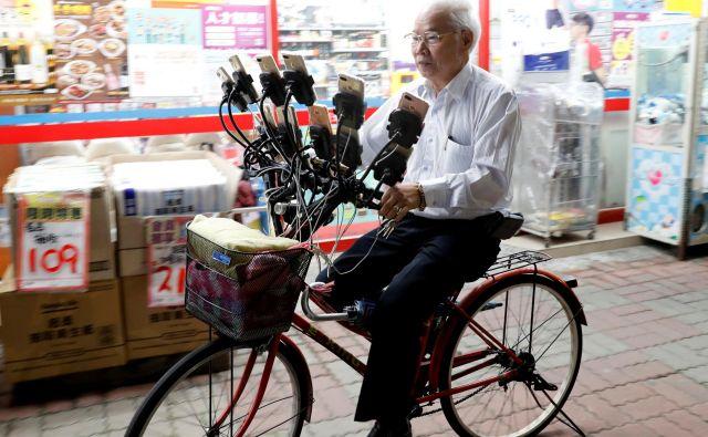 Tajvanski 70-letnik Chen San-yuan, znan kot dedek Pokemon, vozi svoje kolo po ulici v Tajpeju in istočasno igra igrico Pokemon kar na 15. pametnih telefonih.Foto Tyrone Siu Reuters