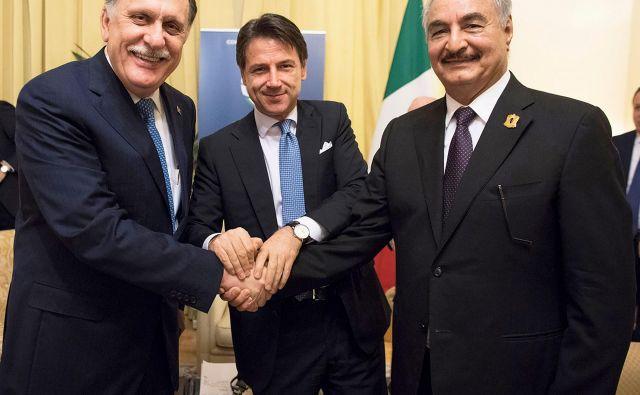 V Palermu sta se sestala najpomembnejša moža v Libiji, vodja iz Tripolija Fajez al Saradž (na fotografiji levo) in vladar vzhodnega dela države general Halifa Haftar (desno, med njima gostitelj, italijanski premier Giuseppe Conte). FOTO: AFP