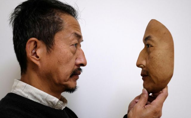Predsednik REAL-f Co. Osamu Kitagawa drži superrealistično masko obraza v tovarni v japonskem Otsu. Foto Kwiyeon Ha Reuters