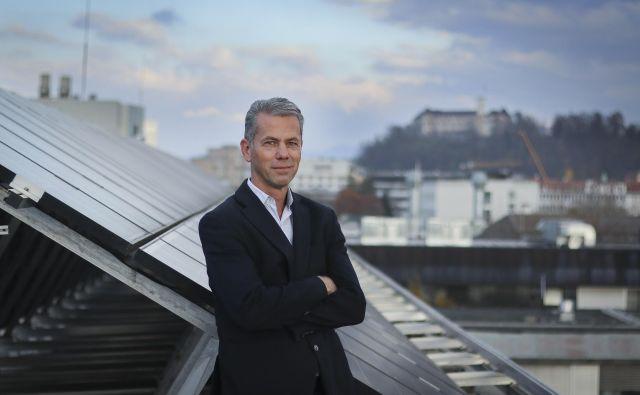 Dr. Marko Topić lahko proizvodnjo sončne elektrarne na strehi Fakultete za elektrotehniko preveri kadar koli v aplikaciji. FOTO: Jože Suhadolnik/Delo