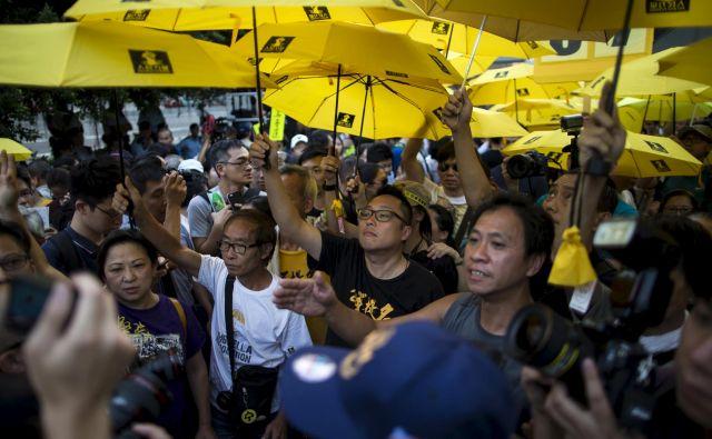 Na tisoče ljudi, zlasti študentov, se je leta 2014 udeležilo protestov v središču Hongkonga. Ker so jih oblasti hotele razgnati s solzivcem, so se zaščitili z dežniki, po katerih je gibanje dobilo ime. FOTO: Reuters
