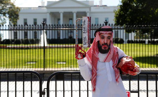 Protestnik v obleki savdskega prestolonaslednika stoji pred Belo hišo z žago za meso in odrezano glavo lutke umorjenega novinarja. FOTO: Reuters