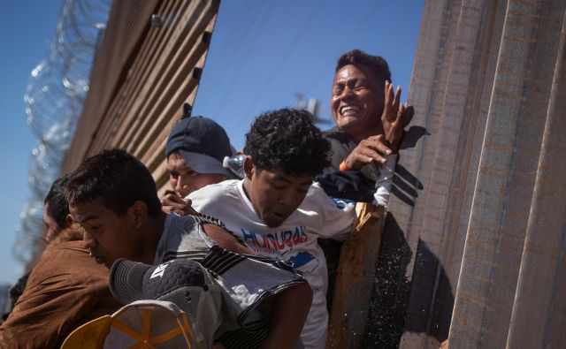 Več sto ljudi je poskusilo prek ograje vdreti na ameriško ozemlje, obmejna policija jih je odgnala s solzivcem. Foto Reuters