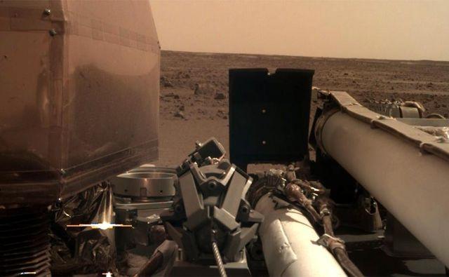Kamera, ki bo skrbela za pravilno postavitev znanstvenih instrumentov na robotski roki landerja, je posnela fotografijo območja pristanka. Na posnetku je še viden prozoren filter, da so kamero zaščitili proti prahu, ki se je dvignil ob pristanku. FOTO: NASA/JPL-Caltech