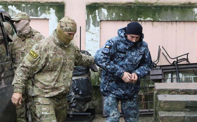 Član ruske Zvezne varnostne službe (FSB) vodi ukrajinskega mornarja na zaslišanje.FOTO: Pavel Rebrov/Reuters
