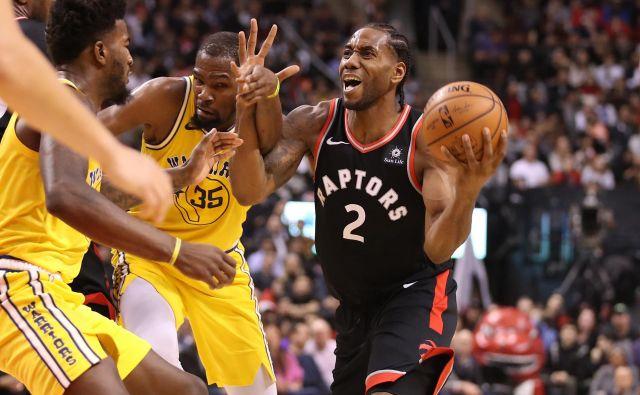 Kawhi Leonard (z žogo) je bil med najzaslužnejšimi za zmago moštva Toronto Raptors nad Golden State Warriors. FOTO: Reuters