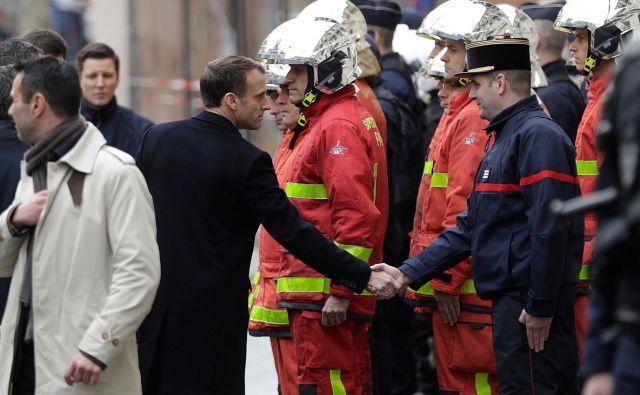 Francoski predsednik pozdravlja pripadnike gasilskih enot, ki so posredovali pri gašenju požarov na desetine požarov v središču Pariza. FOTO: Geoffroy VAN DER HASSELT / AFP