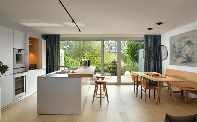 Pri prenovi so zamenjali položaj kuhinje in dnevnega prostora, tako da je kakovostnejši del pritličja, kjer je veliko naravne svetlobe, pripadel kuhinji in jedilnici. Kuhinja je bela in izčiščena. Foto: Miran Kambič