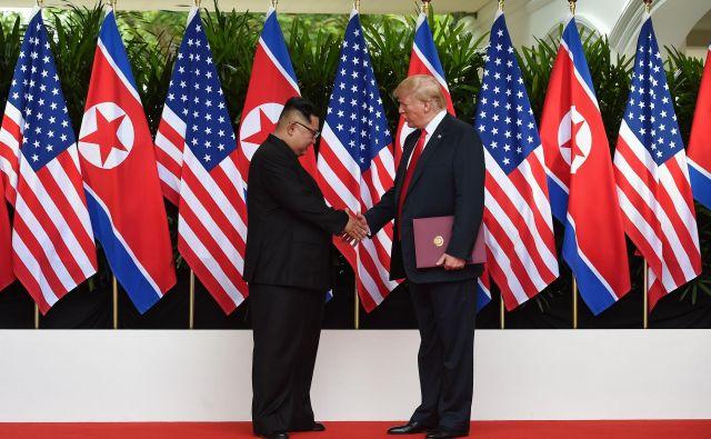 Severnokorejski voditelj Kim Džong Un se rokuje s predsednikom ZDA Donaldom Trumpom. FOTO Anthony Wallace / POOL / AFP