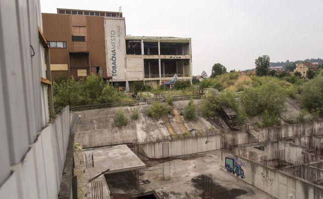 Gradbena jama na območju Tobačne bo zevala še najmanj pol leta. Usoda prodaje nepremičnin propadlega Imosa-G je zdaj v rokah ustavnih sodnikov. Foto Voranc Vogel