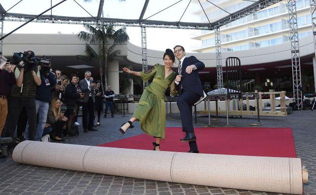 Takole sta igralka Sandra Oh in komik Andy Samberg razvila rdečo preprogo, po kateri se bodo sprehodili zvezdniki. FOTO: AFP