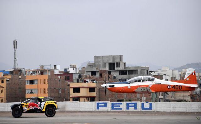Portret Francoza Sebastiena Loeba v svojem Peugeotu med ekshibicijsko dirko proti letalu pred uradnim začetkom relija Dakar v Peruju. Foto Franck Fife Afp