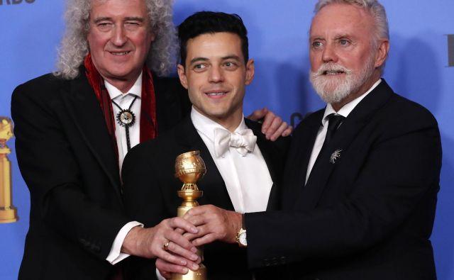 Rami Malek na nedeljski podelitvi zlatih globusov s članoma zasedbe Queen, kitaristom Brianom Mayem in bobnarjem Rogerjem Taylorjem. FOTO: Reuters