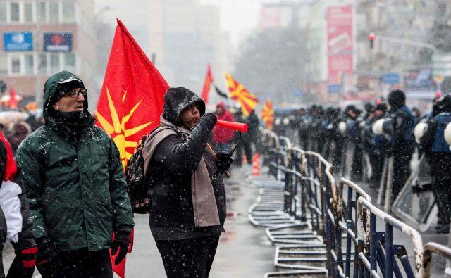 Protestov proti spremembi imena države se je v sredo pred močno zastraženo stavbo parlamenta udeležila manjša skupina ljudi. FOTO: AFP