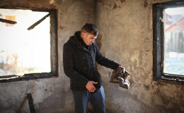 Alžirec Abdul Mamun v svoji sobi, ki je pred kratkim pogorela. Edino, kar je 22-letniku ostalo, so pohodni čevlji. Možnosti, da ga bodo ponesli v obljubljeno deželo Evropo, je vse manj. FOTO: Jure Eržen/Delo