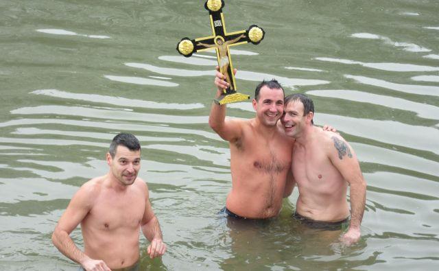Zmagovalec plavanja za križ v Savinji je letos Ljubiša Šolajić (v sredini s križem), desno je David Tepić, levo podpredsednik Zveze srbske diaspore Slovenije Igor Mitić. FOTO: Špela Kuralt/Delo