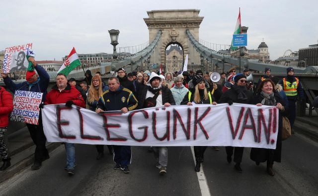 »Dovolj imamo!« je sporočilo, ki ga protestniki z ulic pošiljajo Viktorju Orbanu instranki Fidesz. FOTO: Ferenc Isza/AFP