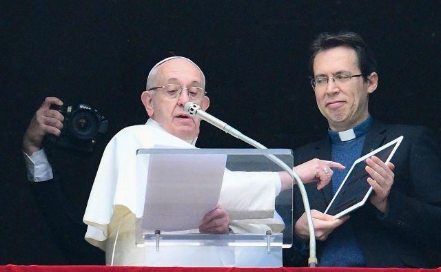 Papež Frančišek in pater Fornos, mednarodni direktor Apostolata molitve, vernikom na Trgu sv. Petra v Rimu na ipadu predstavljata aplikacijo za molitev <em>click to pray</em>. FOTO: AFP