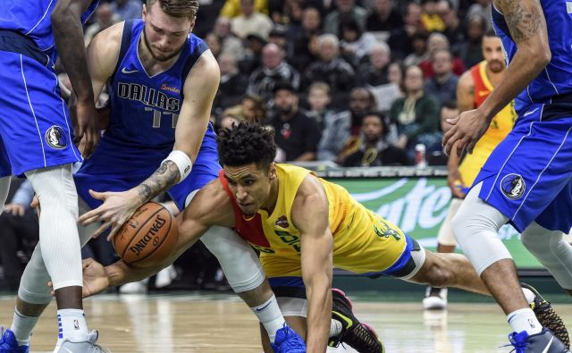 Luka Doncic se je takole boril za žogo z Malcolmom Brogdonom. FOTO: Reuters