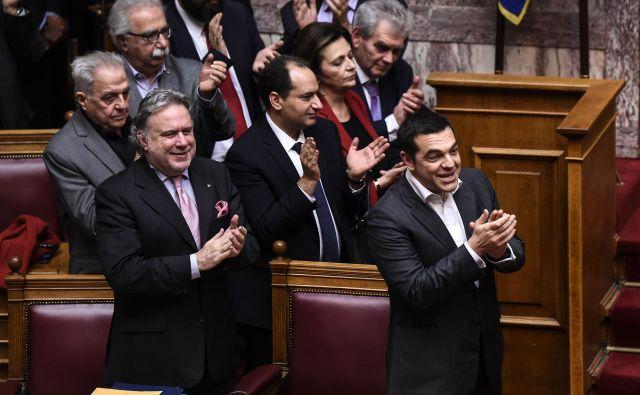 Grški premier Aleksis Cipras skupaj s člani svoje vlade po ratifikaciji prespanskega sporazuma v grškem parlamentu. FOTO: Angelos Tzortzinis/Afp