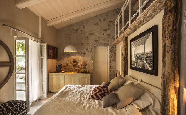 Kamniti zidovi, stari leseni tramovi, rustikalno pohištvo in svetila, ki spominjajo na svetlobne instalacije, zaznamujejo staro, a prenovljeno hišo na italijanskem otoku Elba. FOTO: Adriano Bacchella