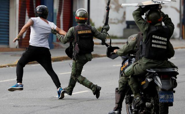 Pripadniki venezuelskih varnostnih sil lovijo protestnika med januarskimi protivladnimi demonstracijami v Caracasu, med katerimi je bilo pridržanih 740 ljudi. FOTO: Reuters