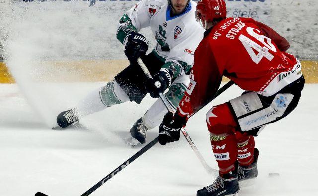 Kot ponavadi je bilo v derbiju precej zanimivih dvobojev, kot je ta med Olimpijinim napadalcem Žanom Jezovškom in Jeseničanom Nejcem Stojanom. FOTO Roman Šipić/Delo
