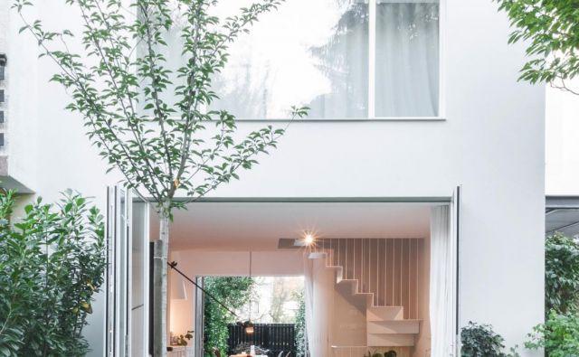 Pritlični del stanovanja se na obeh straneh podaljša v zunanje prostore. Na eni strani v dvoriščni, torej vstopni prostor, na drugi na manjši vrt. Na vzhodni strani, kjer je vhod v hišo, so dvorišče tlakovali in ga ozelenili, prav tako je fasada prizidka ozelenjena z bršljanom. FOTO: Boris Vranić