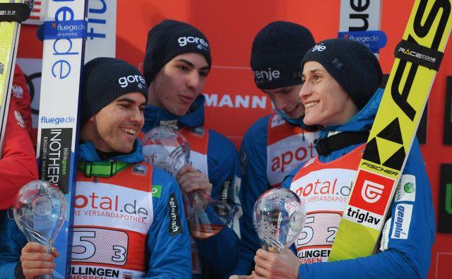 Slovenski skakalci Jernej Damian, Timi Zajc, Anže Semenič in Peter Prevc so se v petek veselili ekipnega 3. mesta, danes pa bodo izvedeli, kdo potuje na SP v Avstriji. FOTO: Arne Dedert/AFP