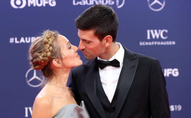 Novak Đoković v objemu soproge Jelene. FOTO: Valery Hache/AFP