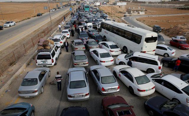 Domačini in trgovci potrpežljivo čakajo na vstop v državo. FOTO: Muhammad Hamed/Reuters