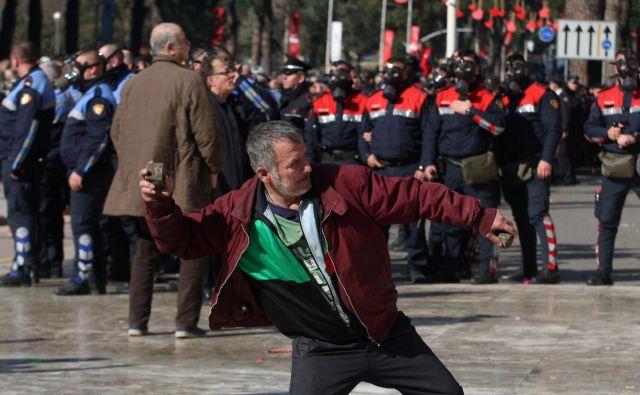 Protestniki pred vladnim poslopjem so policiste obmetavali s kamenjem. FOTO: Florion Goga/Reuters